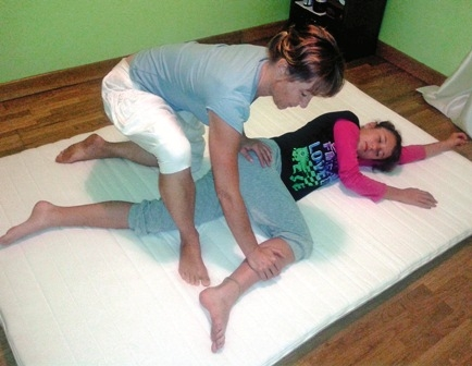 Thai massage takes place on a floor mat with the client fully dressed