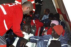 Red Cross workers treat migrants from a previous arrival