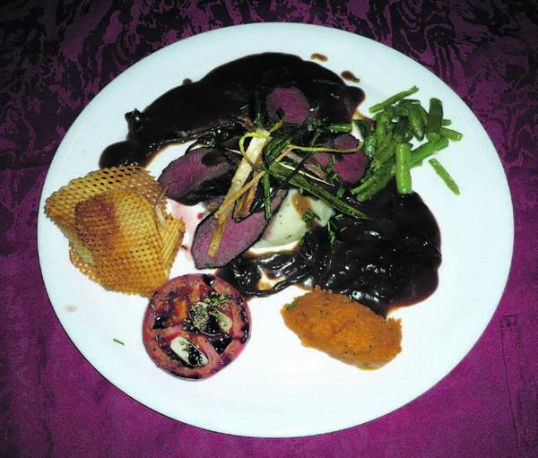 Hirschlende, serviert auf wilden Pilzen mit Schalotten in Rotweinsauce