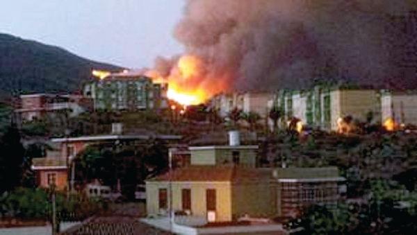 Dramatisch: Hell lodern die Flammen direkt hinter einer Ortschaft auf.