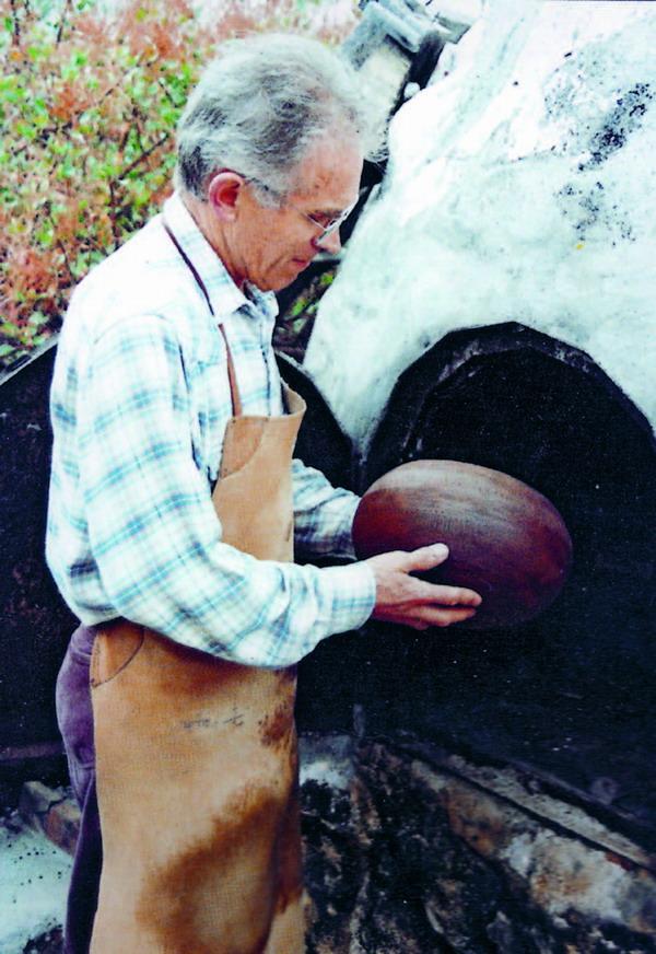 Ramón Barreto Leal mit einem Keramikgefäß vor dem Töpferofen