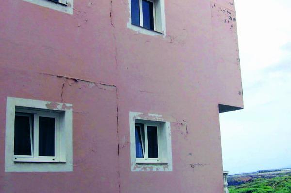 An der Fassade dieses Hauses sind die Fugen zwischen Pfeiler und Geschossdecke eindeutig durch Putzrisse markiert
