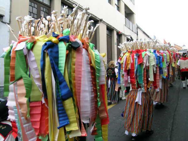 Unter den schweren Körben mit den phantasievollen Figuren und farbenfrohen Bändern sind die jungen Frauen kaum zu sehen.