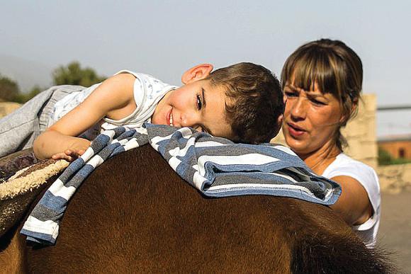 Martina mit einem Schützling, für den das Glück der Erde tatsächlich auf dem Rücken eines Pferdes liegt.